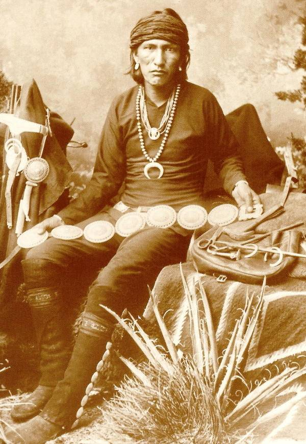 Portrait of Navajo Silversmith Bai-De-Schluch-A-Ichin (Slender Silversmith) in Native Dress with Silver Necklaces, Concho Belts, Tools and Army Saddle Bag 1883 - Creator: Wittick, George Ben