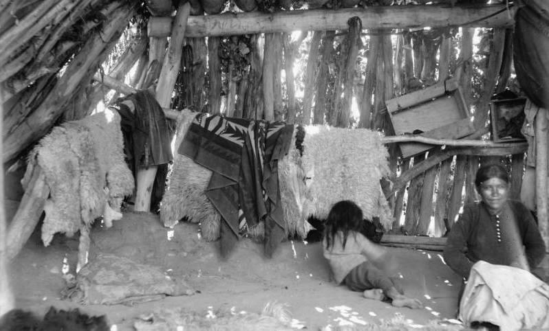 Baby and Navajo woman interior of summer hogan.
