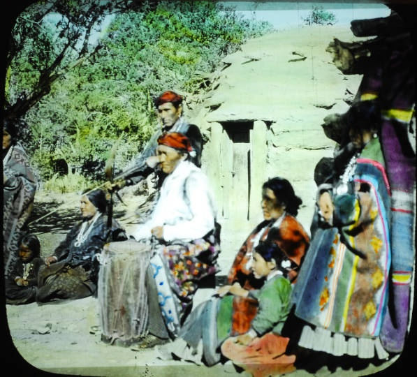 Navajo Medicine man sits in front of hogan with his family
