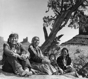 Navajo family sitting on ground by tree. Monument Valley, 1960's.