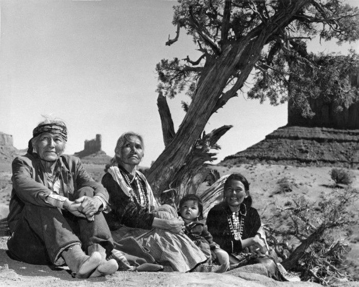 Navajo family sitting on ground by tree. Monument Valley, 1960's
