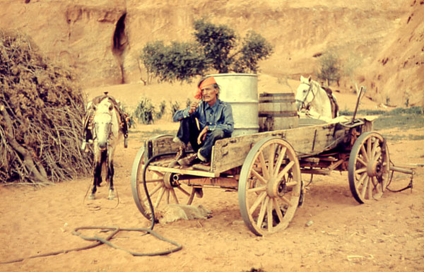 Navajo Man sitting in wagon, two barrels in the back of wagon, two horses on the side of the wagon