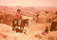 Man, wearing a red shirt and cowboy hat, riding a horse. Woman sitting on ground next to the side of them