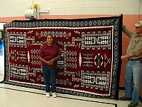 Weaver Showing here Large Storm Pattern Navajo Rug